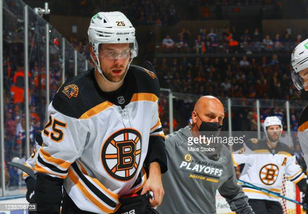 Brandon Carlo of the Boston Bruins is tended to by the trainer during the third period against the New York Islanders in Game Three of the Second...