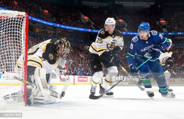 Brandon Carlo of the Boston Bruins looks as Jaroslav Halak of the Boston Bruins makes a save off the shot of Brandon Sutter of the Vancouver Canucks...
