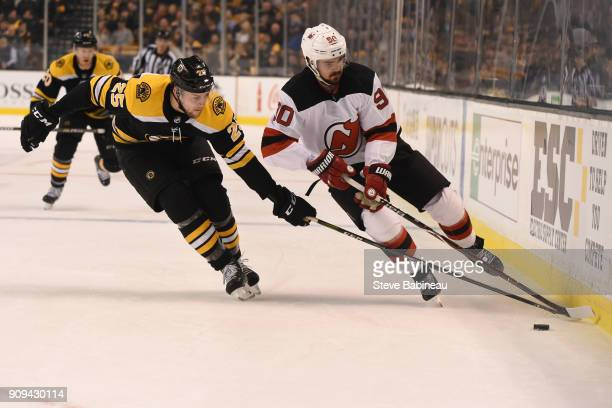 Brandon Carlo of the Boston Bruins reaches for the puck against Marcus Johansson of the New Jersey Devils at the TD Garden on January 23 2018 in...