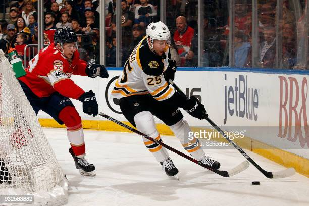 Brandon Carlo of the Boston Bruins skates with the puck against Maxim Mamin of the Florida Panthers at the BBT Center on March 15 2018 in Sunrise...