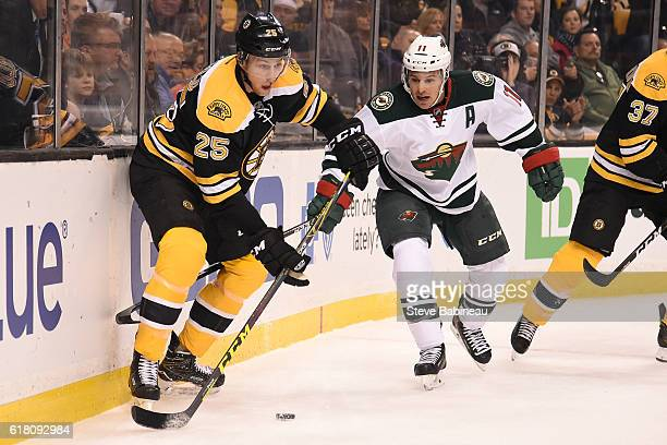 Brandon Carlo of the Boston Bruins skates with the puck against Zach Parise of the Minnesota Wild at the TD Garden on October 25 2016 in Boston...