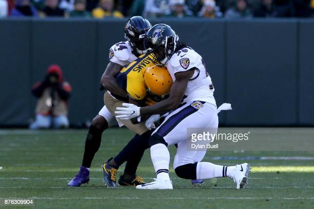 Brandon Carr and Tim Williams of the Baltimore Ravens combine for a tackle against Davante Adams of the Green Bay Packers in the second quarter at...