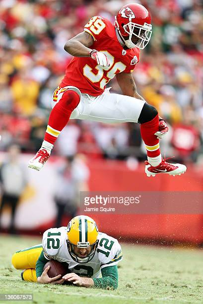 Brandon Carr of the Kansas City Chiefs leaps over a sliding quarterback Aaron Rodgers of the Green Bay Packers during the game on December 18 2011 at...