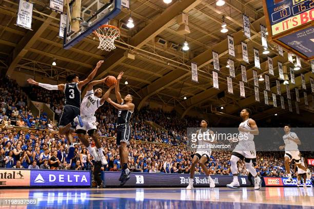 Brandon Childress of the Wake Forest Demon Deacons drives between Tre Jones and Cassius Stanley of the Duke Blue Devils during the first half of...