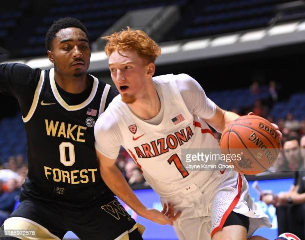 Brandon Childress of the Wake Forest Demon Deacons guards Nico Mannion of the Arizona Wildcats as he drives to the basket in the first half of the...