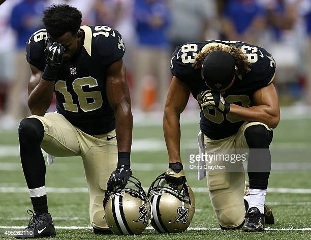 Brandon Coleman and Willie Snead of the New Orleans Saints take a knee after Khiry Robinson was injured in the second quarter of a game against the...