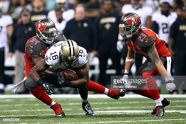 Brandon Coleman of the New Orleans Saints is brought down by George Johnson and Chris Conte of the Tampa Bay Buccaneers during the third quarter of a...
