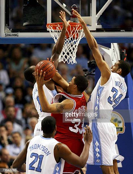 Brandon Costner of the North Carolina State Wolfpack is stopped by Marcus Ginyard and Brandan Wright of the North Carolina Tar Heels in the ACC Men's...