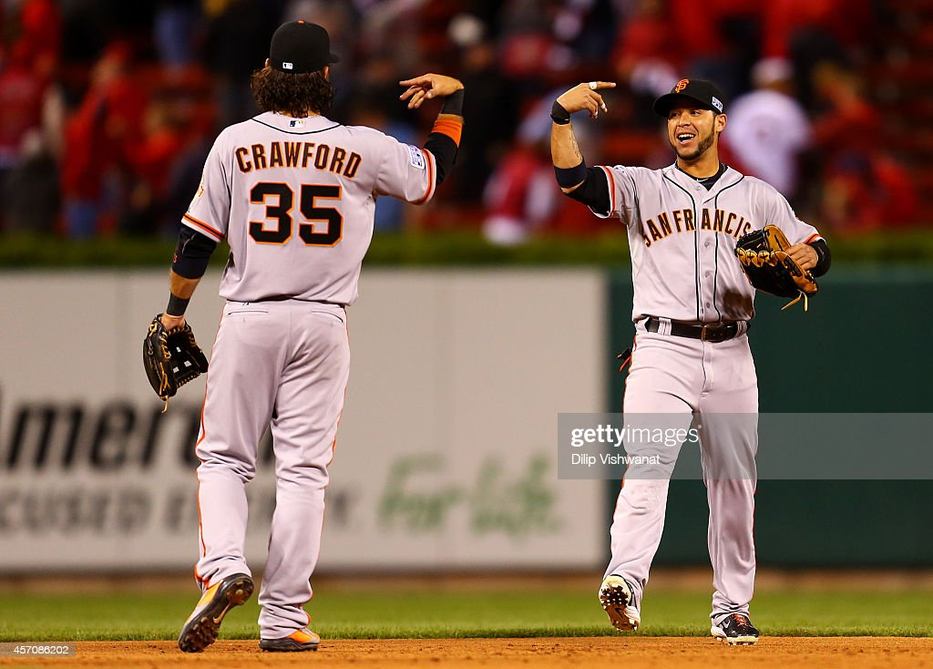 Brandon Crawford #35 and Gregor Blanco #7 of the San Francisco Giants celebrate after their 3 to 0 win over the St. Louis Cardinals during Game One of the National League Championship Series at Busch Stadium on October 11, 2014 in St Louis, Missouri.