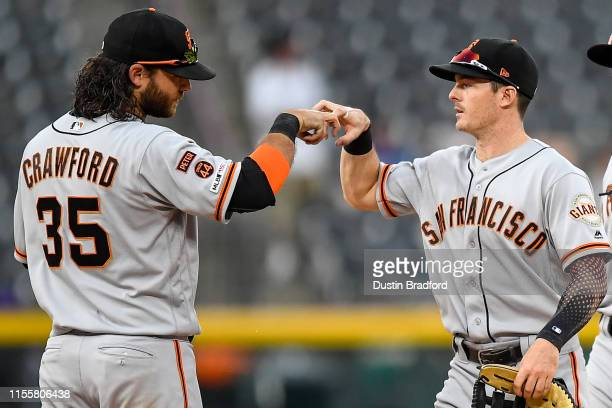Brandon Crawford and Mike Yastrzemski of the San Francisco Giants celebrate after a 192 win over the Colorado Rockies during game one of a...
