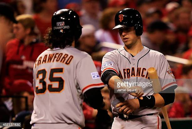Brandon Crawford of the San Francisco Giants celebrates with Buster Posey after scoring on a single by Gregor Blanco in the seventh inning against...