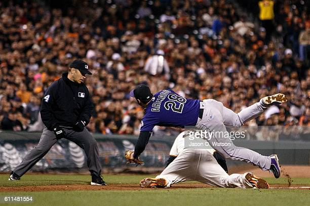 Brandon Crawford of the San Francisco Giants dives into third base ahead of a tag by Nolan Arenado of the Colorado Rockies in front of umpire Mark...
