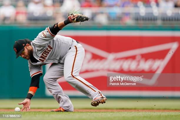 Brandon Crawford of the San Francisco Giants fields an infield single hit by Michael A Taylor of the Washington Nationals in the fifth inning at...