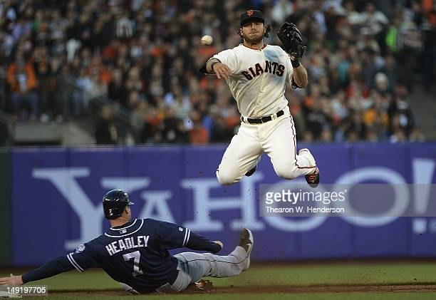 Brandon Crawford of the San Francisco Giants gets his throw off to complete the doubleplay while leaping over the sliding Chase Headley of the San...