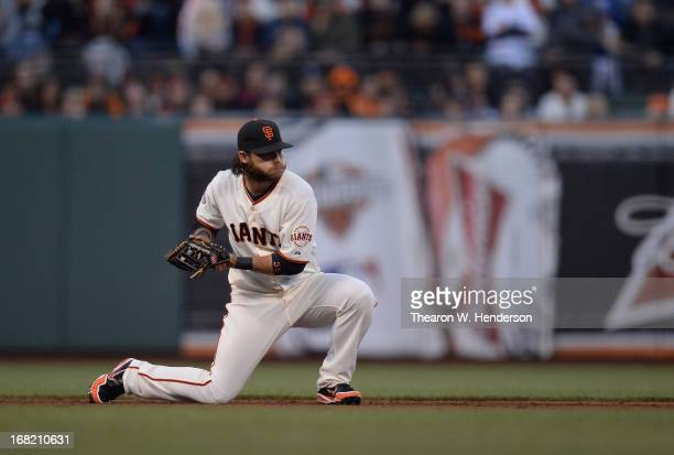Brandon Crawford of the San Francisco Giants goes down to one knee to field the ball and make a throw to second base against he Los Angeles Dodgers...