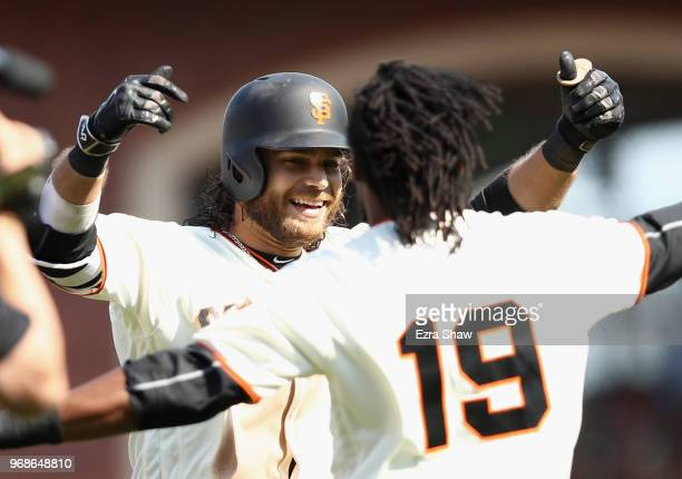 Brandon Crawford of the San Francisco Giants is congratulated by Alen Hanson after he hit a single that scored the winning run in the bottom of the...