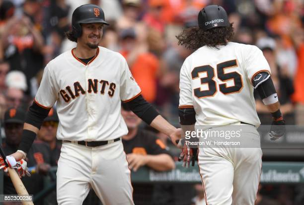 Brandon Crawford of the San Francisco Giants is congratulated by Jarrett Parker after Crawford hit a solo home run against the Colorado Rockies in...