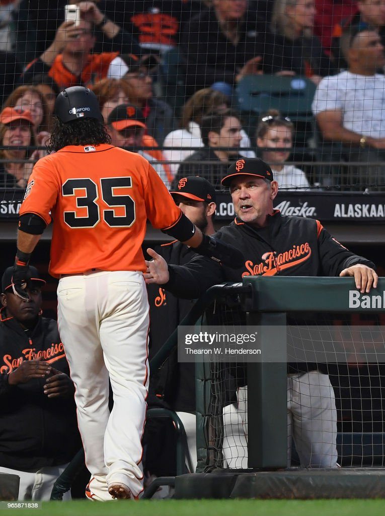 Brandon Crawford #35 of the San Francisco Giants is congratulated by manager Bruce Bochy #15 after Crawford scored against the Philadelphia Phillies in the bottom of the fourth inning at AT&T Park on June 1, 2018 in San Francisco, California.