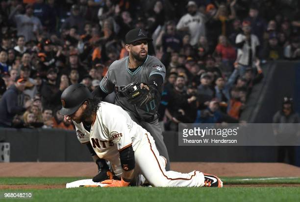Brandon Crawford of the San Francisco Giants is safe at third base sliding in before the tag of Deven Marrero of the Arizona Diamondbacks in the...