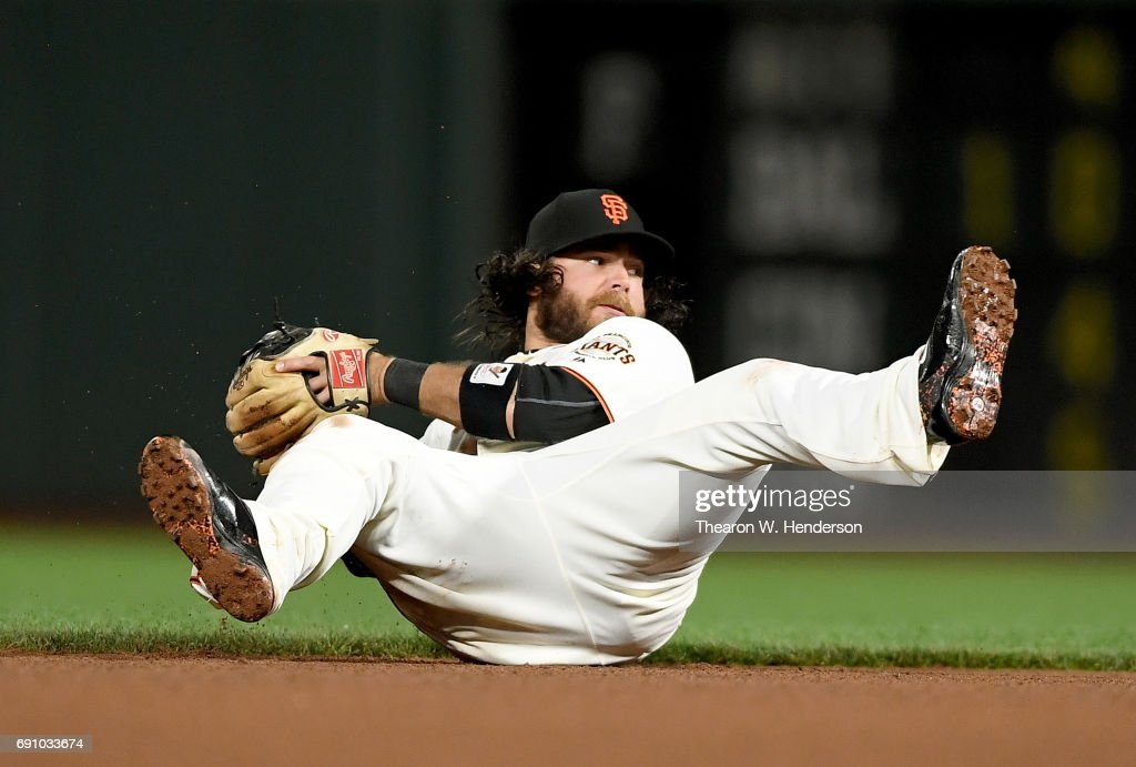 Brandon Crawford #35 of the San Francisco Giants looks to throw to first base from the seat of his pants against the Washington Nationals in the top of the seventh inning at AT&T Park on May 31, 2017 in San Francisco, California.