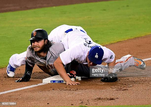 Brandon Crawford of the San Francisco Giants reacts after he is tagged out at third base by Corey Seager of the Los Angeles Dodgers to end the top of...