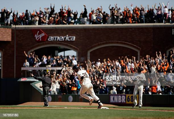 Brandon Crawford of the San Francisco Giants rounds first base after hitting a home run to tie their game against the Arizona Diamondbacks in the...
