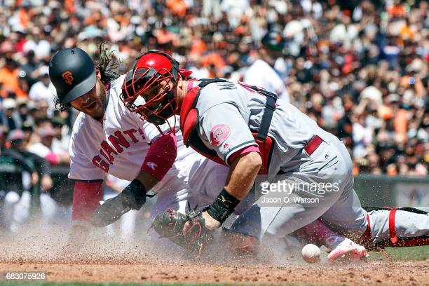 Brandon Crawford of the San Francisco Giants scores a run ahead of a tag from Devin Mesoraco of the Cincinnati Reds during the first inning at ATT...