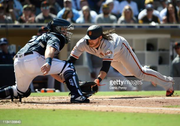 Brandon Crawford of the San Francisco Giants scores ahead of the tag of Austin Hedges of the San Diego Padres during the fifth inning of a baseball...
