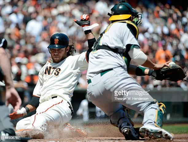 Brandon Crawford of the San Francisco Giants slides in safe at home beating the throw to catcher Kurt Suzuki of the Oakland Athletics in the third...