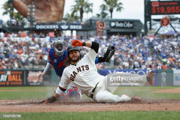 Brandon Crawford of the San Francisco Giants slides in safely at home plate to score on a single hit by Gorkys Hernandez in the bottom of the second...