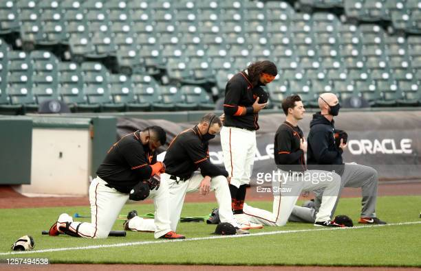 Brandon Crawford stands in the middle of Pablo Sandoval, manager Gabe Kapler, Mike Yastrzemski and coach Andy King of the San Francisco Giants during...