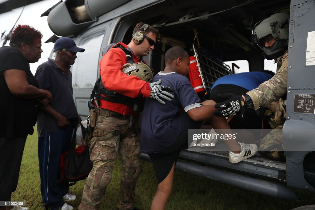 Brandon Daugherty from the Florida Air Force Reserve Pararescue team from the 308th Rescue Squadron helps evacuees born a helicopter after they were rescued from the flooding of Hurricane Harvey on August 30, 2017 in Port Arthur, Texas. Harvey, which made landfall north of Corpus Christi late Friday evening, is expected to dump upwards to 40 inches of rain in Texas over the next couple of days.