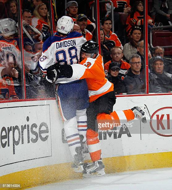 Brandon Davidson of the Edmonton Oilers is checked by Radko Gudas of the Philadelphia Flyers during the third period at the Wells Fargo Center on...