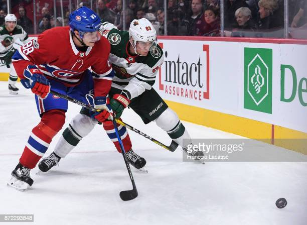 Brandon Davidson of the Montreal Canadiens skates for the puck against Tyler Ennis of the Minnesota Wild in the NHL game at the Bell Centre on...