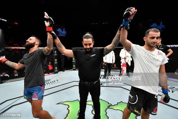Brandon Davis and Giga Chikadze of Georgia react after their featherweight bout is ruled a draw during the UFC Fight Night event at Royal Arena on...