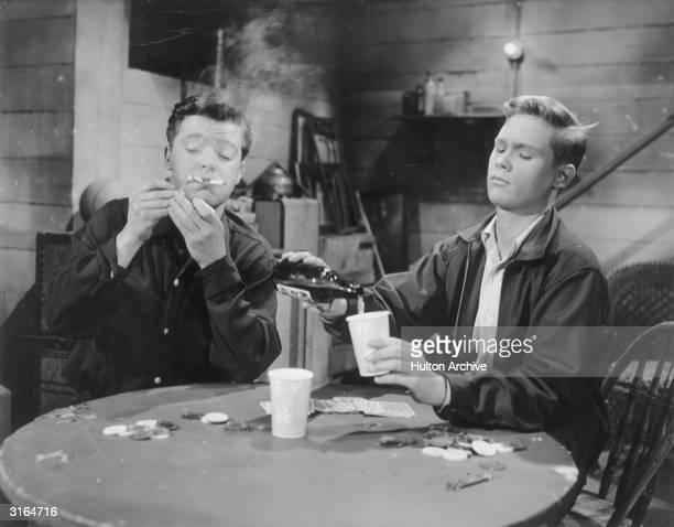 Brandon de Wilde, right , pouring beer during a gambling scene from Philip Dunn's film 'Blue Denim'.