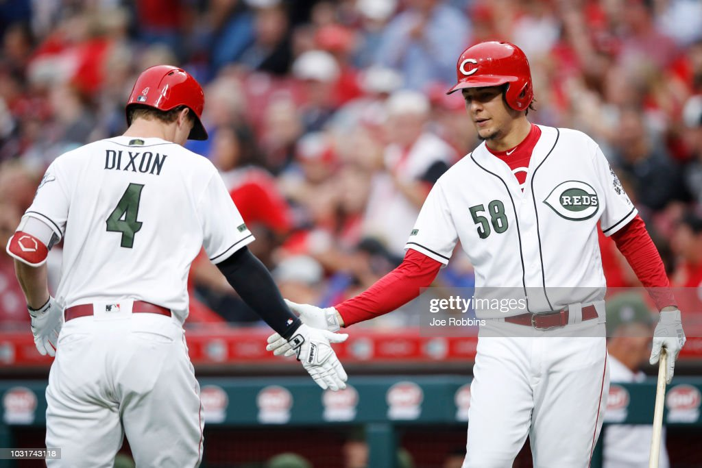 Brandon Dixon #4 of the Cincinnati Reds is congratulated by Luis Castillo #58 after hitting a solo home run in the second inning of the game against the Los Angeles Dodgers at Great American Ball Park on September 11, 2018 in Cincinnati, Ohio. The Reds won 3-1.