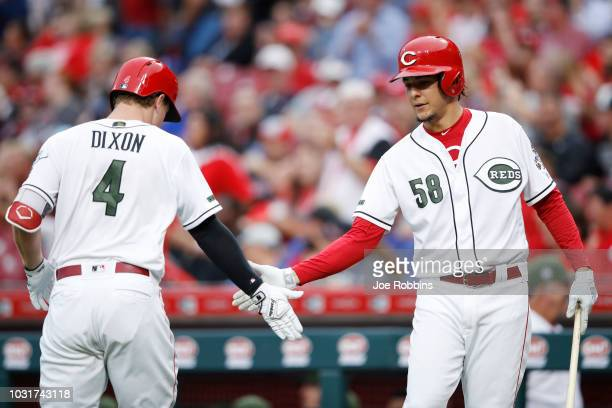 Brandon Dixon of the Cincinnati Reds is congratulated by Luis Castillo after hitting a solo home run in the second inning of the game against the Los...
