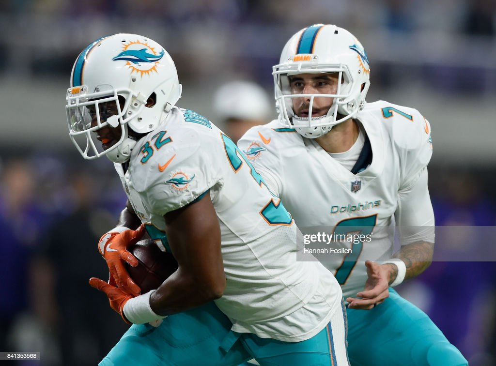Brandon Doughty #7 of the Miami Dolphins hands the ball off to teammate Kenyan Drake #32 during the first quarter in the preseason game against the Minnesota Vikings on August 31, 2017 at U.S. Bank Stadium in Minneapolis, Minnesota.