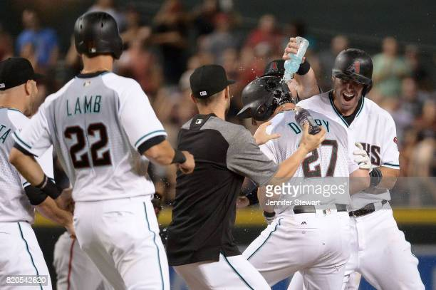 Brandon Drury of the Arizona Diamondbacks celebrates with Chris Owings and Paul Goldschmidt after hitting a walk off single against the Washington...