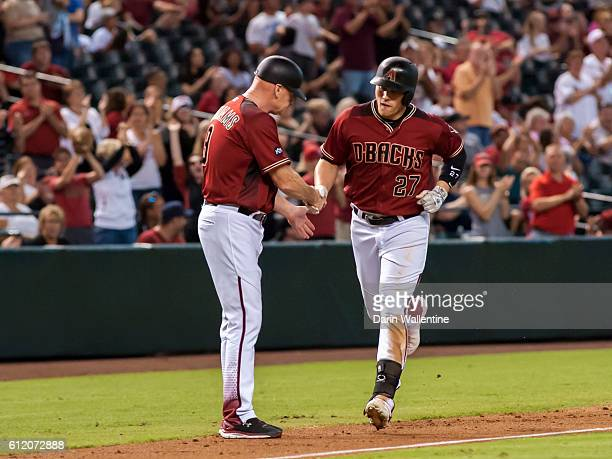 Brandon Drury of the Arizona Diamondbacks homers to right field and is congratulated by third base coach Matt Williams in the eighth inning of the...