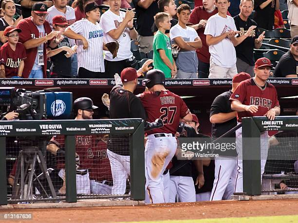 Brandon Drury of the Arizona Diamondbacks is congratulated by his teammates after a home run to right field against the San Diego Padres in the...