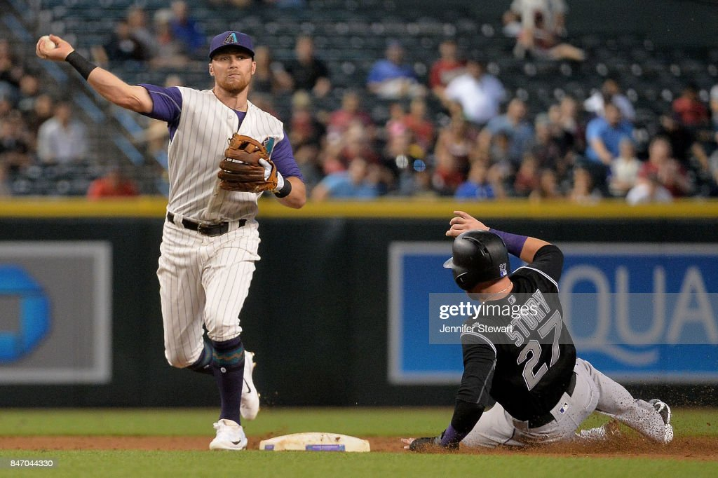 Brandon Drury #27 of the Arizona Diamondbacks turns the double play over Trevor Story #27 of the Colorado Rockies in the second inning at Chase Field on September 14, 2017 in Phoenix, Arizona.