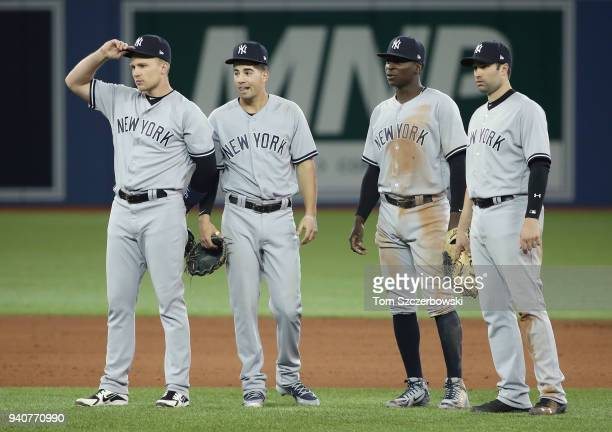 Brandon Drury of the New York Yankees and Tyler Wade and Didi Gregorius and Neil Walker look on and wait during a pitching change in the eighth...