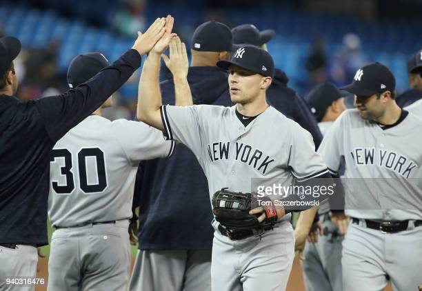Brandon Drury of the New York Yankees celebrates their victory with teammates during MLB game action against the Toronto Blue Jays at Rogers Centre...