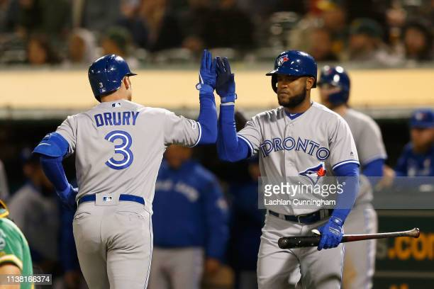 Brandon Drury of the Toronto Blue Jays celebrates with Socrates Brito after hitting a solo home run in the in the top of the fourth inning against...