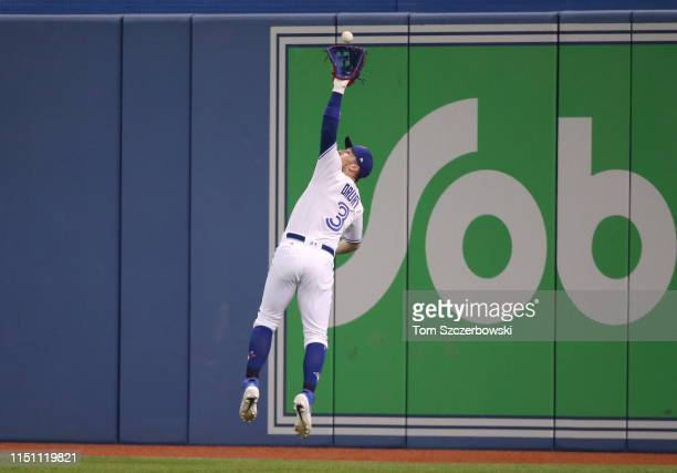 Brandon Drury of the Toronto Blue Jays makes a leaping catch in the eleventh inning during MLB game action against the Boston Red Sox at Rogers...