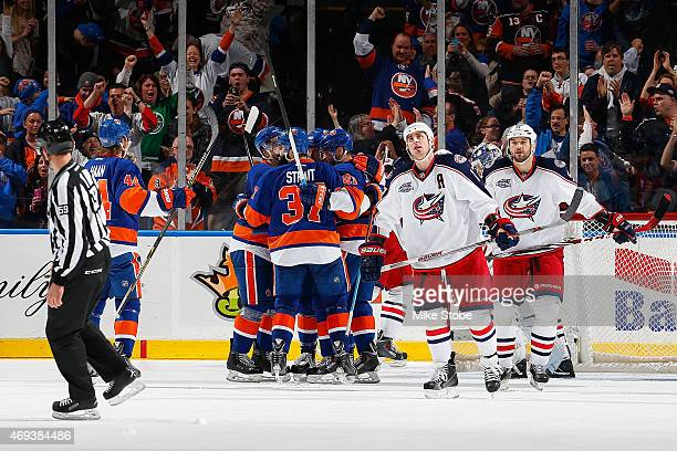 Brandon Dubinsky and Fedor Tyutin of the Columbus Blue Jackets skate away as Kyle Okposo of the New York Islanders is congratulated by his teammates...