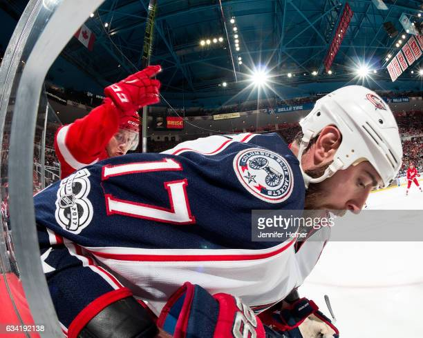 Brandon Dubinsky of the Columbus Blue Jackets and Nick Jensen of the Detroit Red Wings battle for the puck along the boards during an NHL game at Joe...