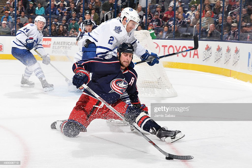 Brandon Dubinsky #17 of the Columbus Blue Jackets continues to play the puck as he is knocked to the ice by Matt Hunwick #2 of the Toronto Maple Leafs during the third period on October 16, 2015 at Nationwide Arena in Columbus, Ohio. Toronto defeated Columbus 6-3.